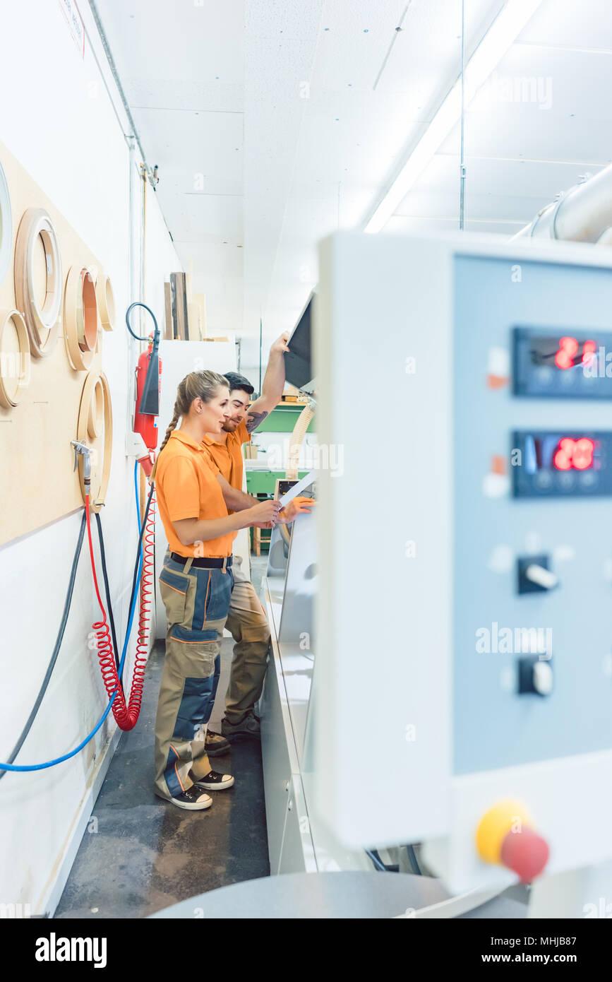 Two carpenters cleaning veneer machine in workshop - Stock Image