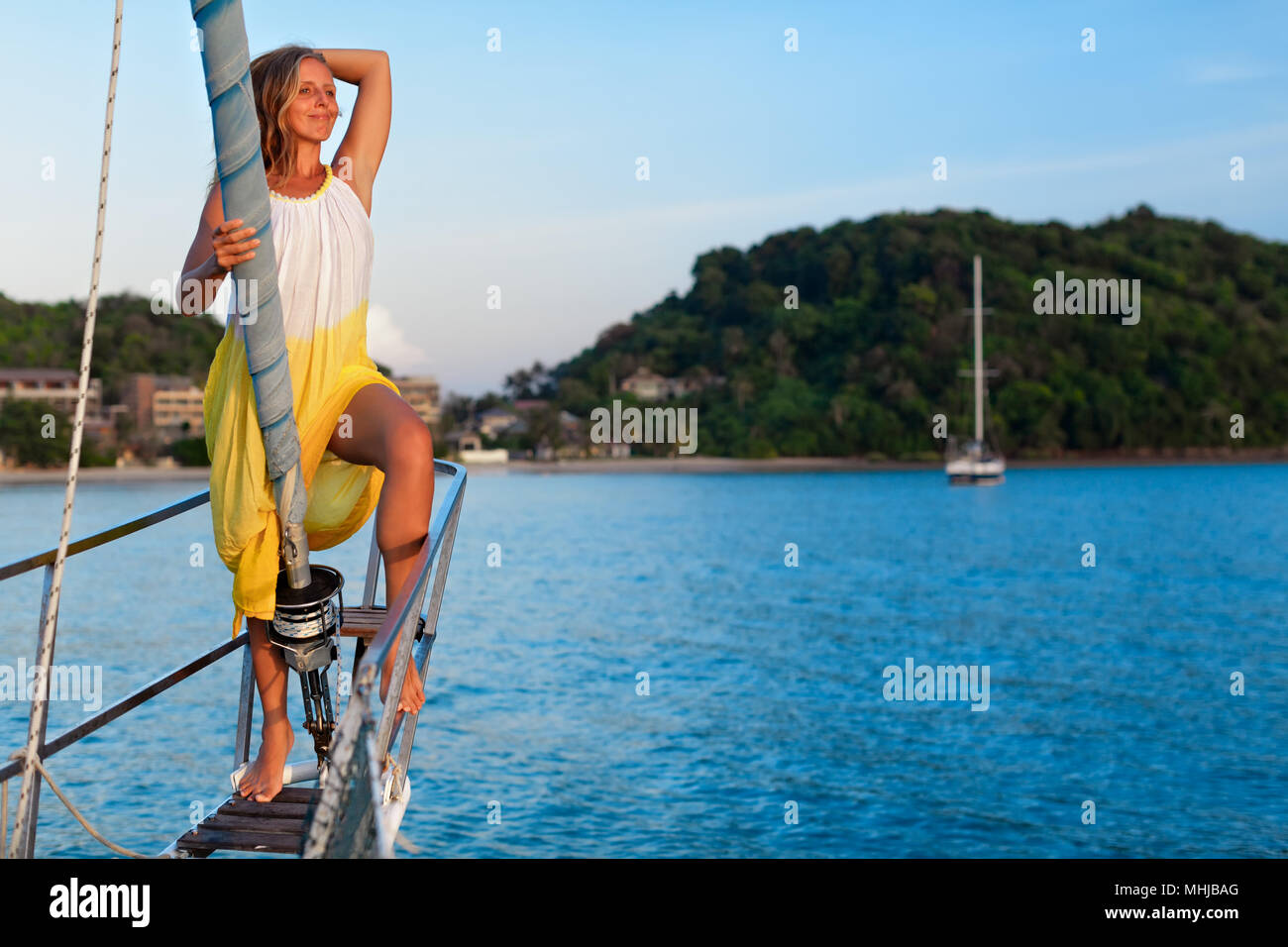 Sailing boat crew on rest. Happy young woman on deck of charter yacht, have fun discovering islands, travel in tropical sea on summer cruise. - Stock Image