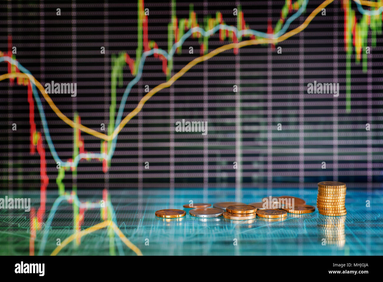 Money and stock market graphs. Coins against futuristic display with candles diagrams - Stock Image