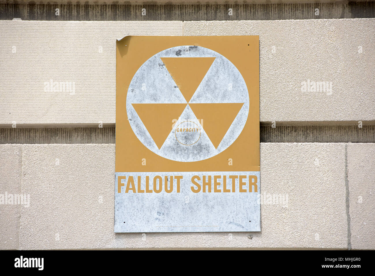 yellow fallout shelter sign on a building - Stock Photo
