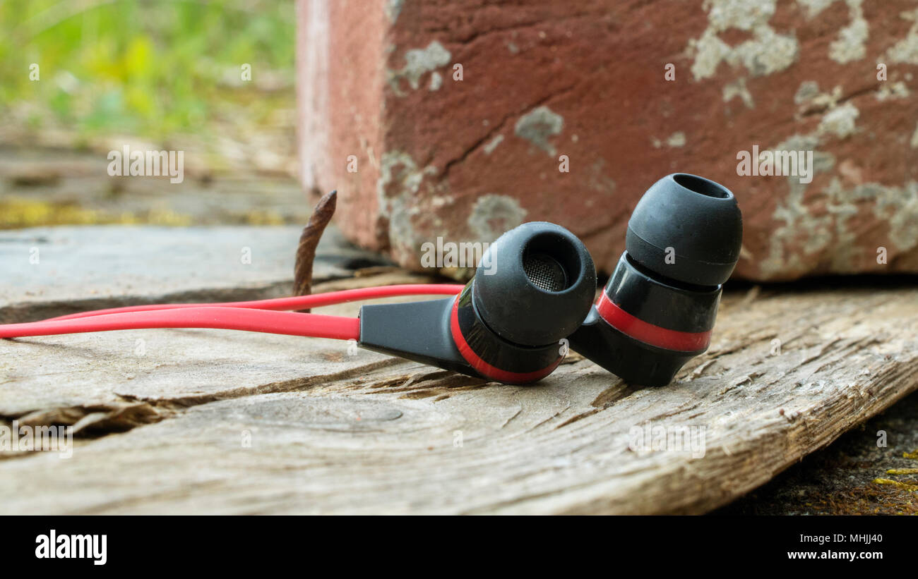 Earbuds lay in the forest combining nature and technology - Stock Image