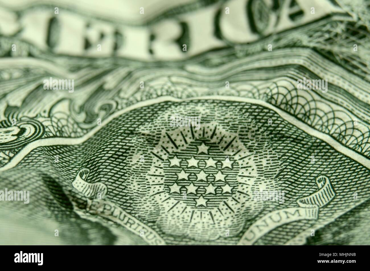 Shallow focus of stars from the great seal on on a wrinkled  American dollar bill. Stock Photo