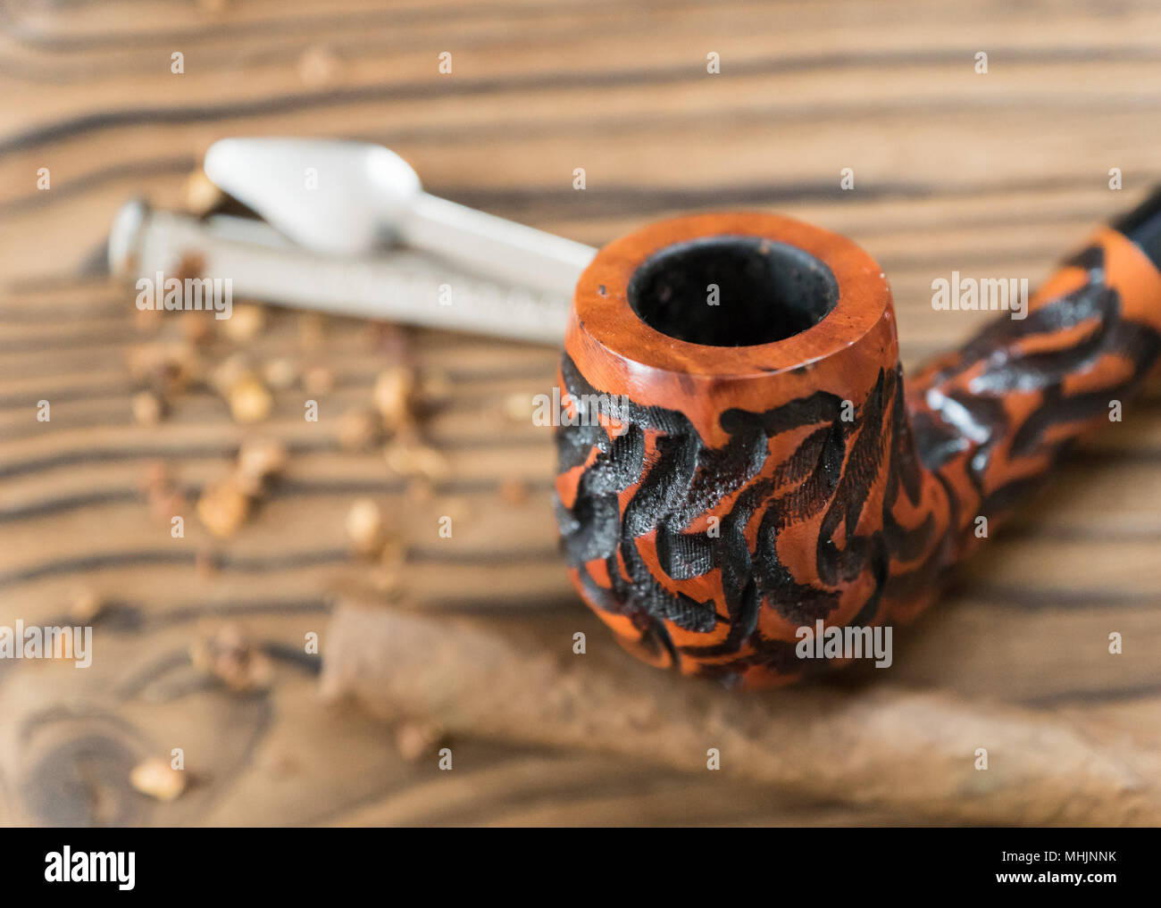 tobacco pipe with tobacco on a brown board - Stock Image