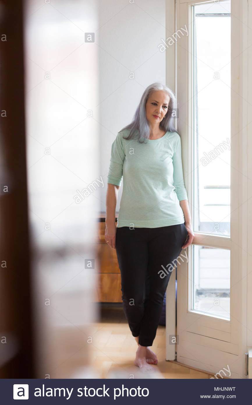 Senior woman standing by window at home - Stock Image
