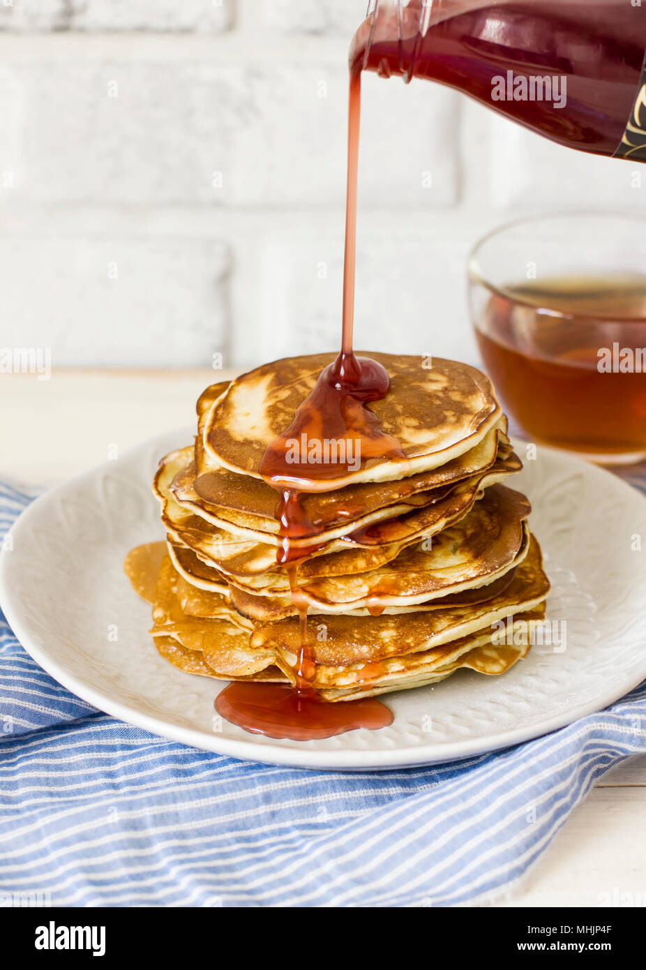 Homemade pancake poured syrup drops in white plate, closeup - Stock Image