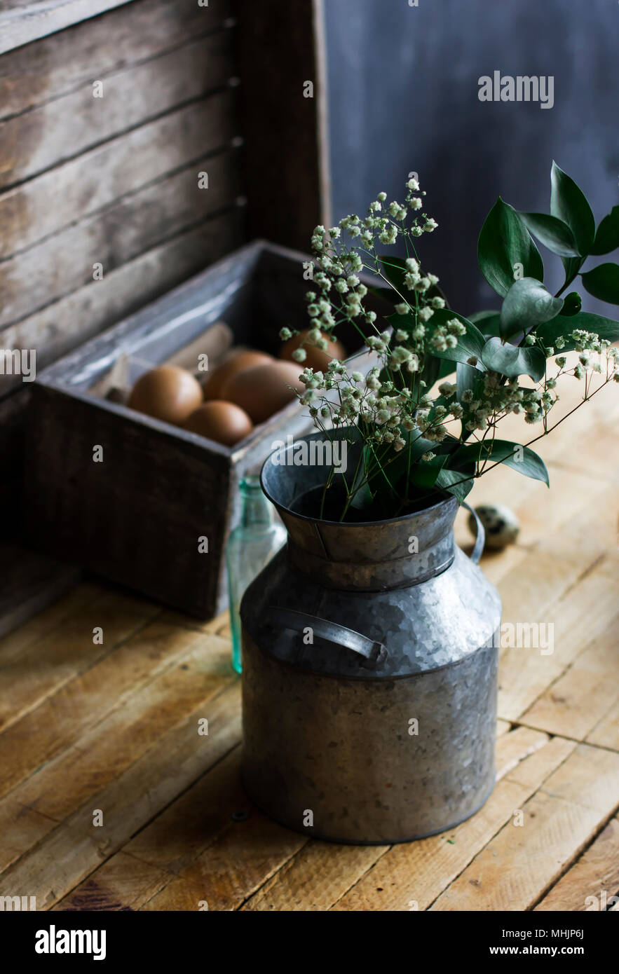 Rustic bouquet of herbs in aluminum cans, chicken eggs in box on the table Stock Photo