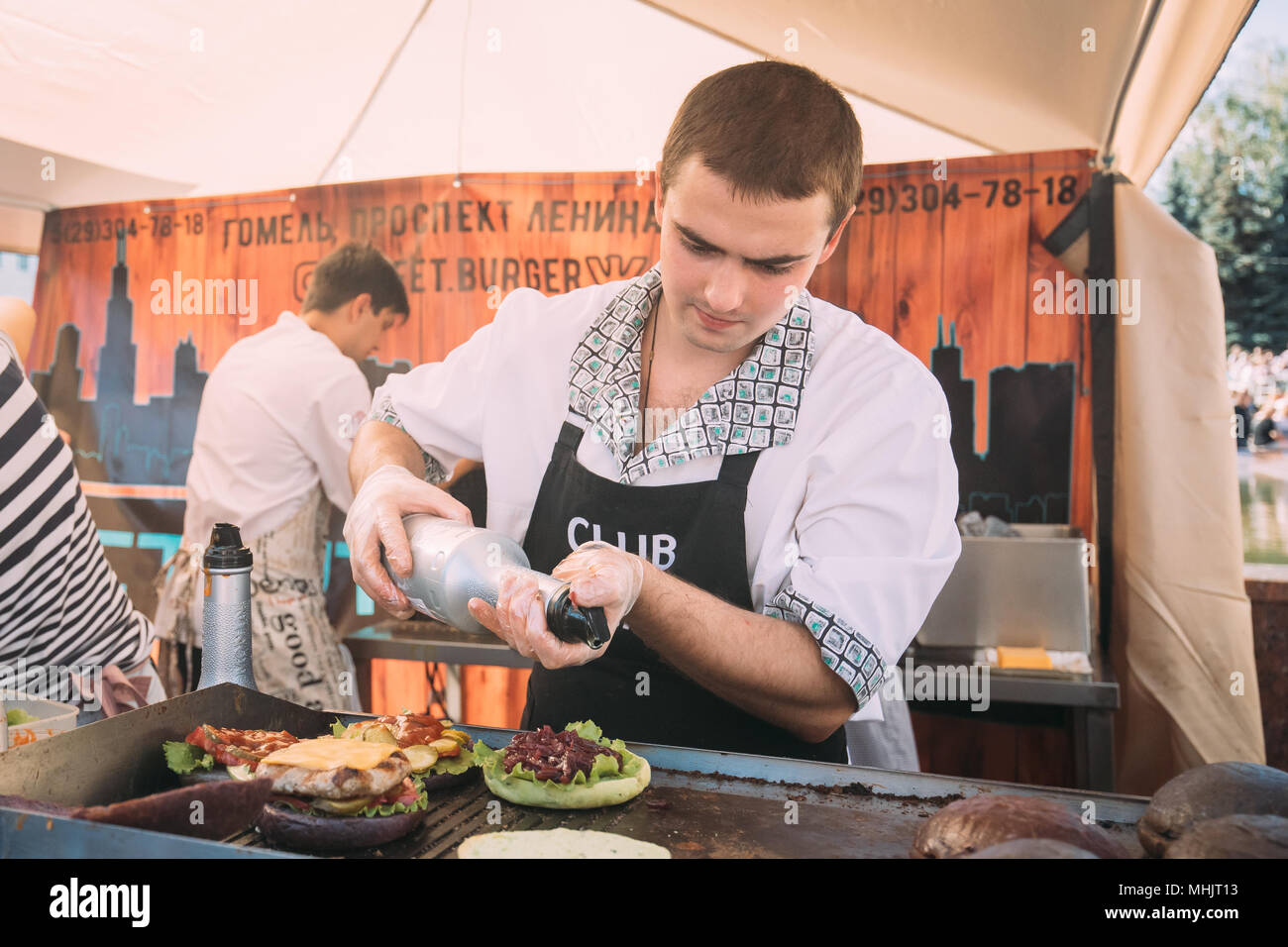 Gomel, Belarus. Man Cooking Burger On Gastronomic Festival City Food In Summer Day. - Stock Image