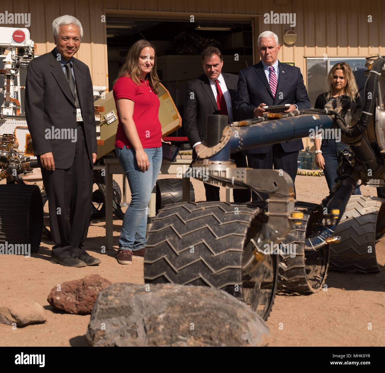 U.S. Vice President Mike Pence uses a remote control to drive a rover nicknamed 'Scarecrow' during a visit to the NASA Jet Propulsion Laboratory Mars Yard April 28, 2018 in Pasadena, California. Standing from left to right are: NASA Mars Exploration Manager Li Fuk, Mars Curiosity Engineering Operations Team Chief Megan Lin, JPL Director Michael Watkins, Vice President Mike Pence, Karen Pence, daughter Charlotte Pence. - Stock Image