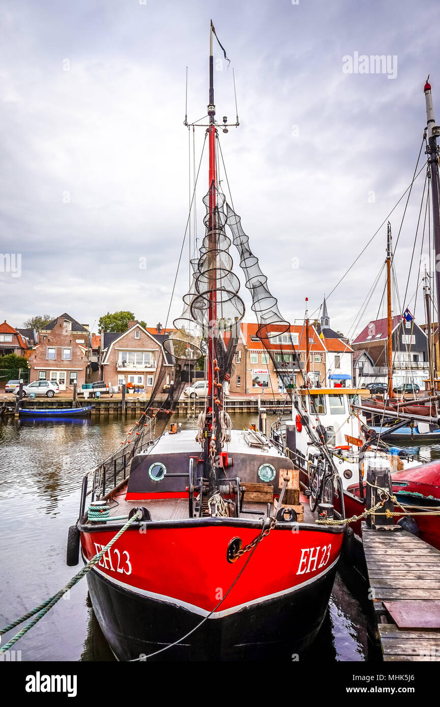 A traditional fishing boat moored at the dock in the harbor of the icturesque village of Urk along the Ijsselmeer in the Netherlands - Stock Image