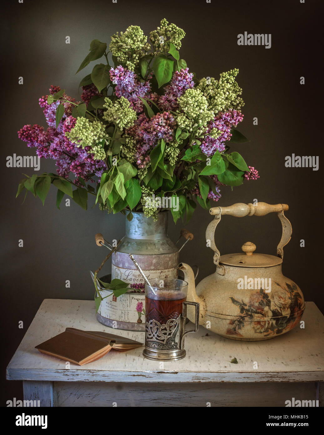 still life with flowers and a glass of tea. vintage.silence. book. kettle. - Stock Image