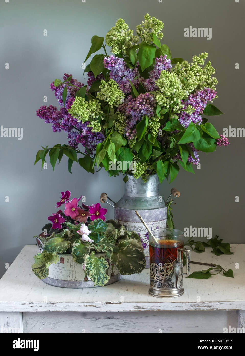 still life with flowers and a glass of tea. vintage, lilac, violets. - Stock Image