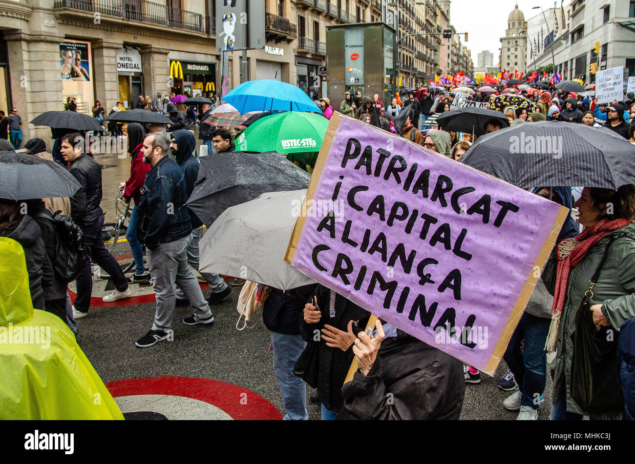 A poster with the text 'patriarchy and capital is a criminal alliances' is seen during the demonstration against job insecurity in Barcelona. Under the celebration of the first of May also some  organizations more concerned about social rights have come out in demonstration in the center of Barcelona to fight against job insecurity and decent work. - Stock Image