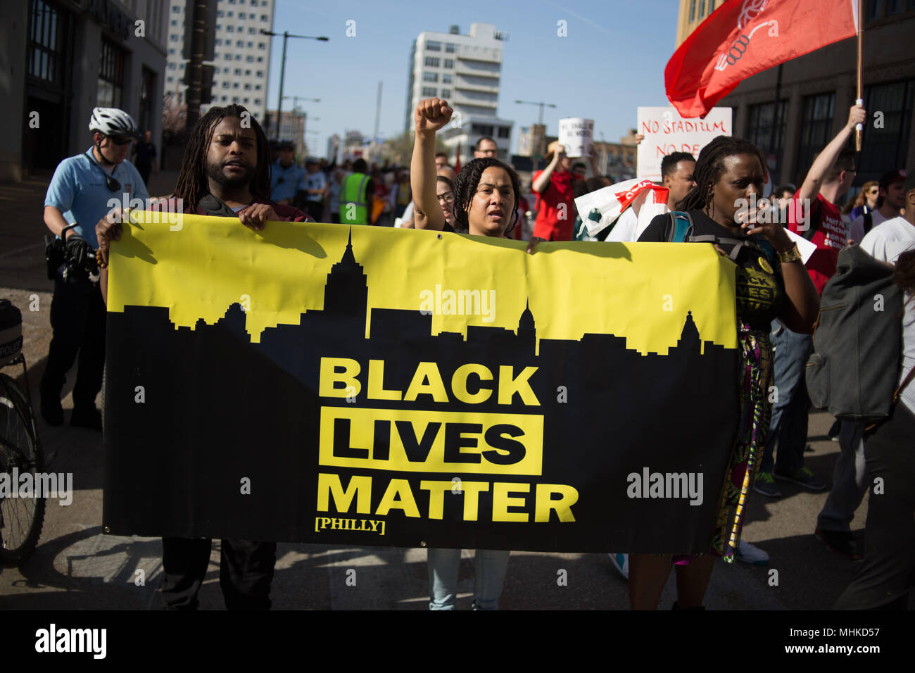 Philadelphia, USA. 1st May 2018. Protestors associated with the 'Stadium Stompers' march down Broad Street to voice opposition to the construction of a new athletic stadium adjacent to Temple University's campus in North Philadelphia, as part of May Day events in the city. Credit: Michael Candelori/Alamy Live News - Stock Image