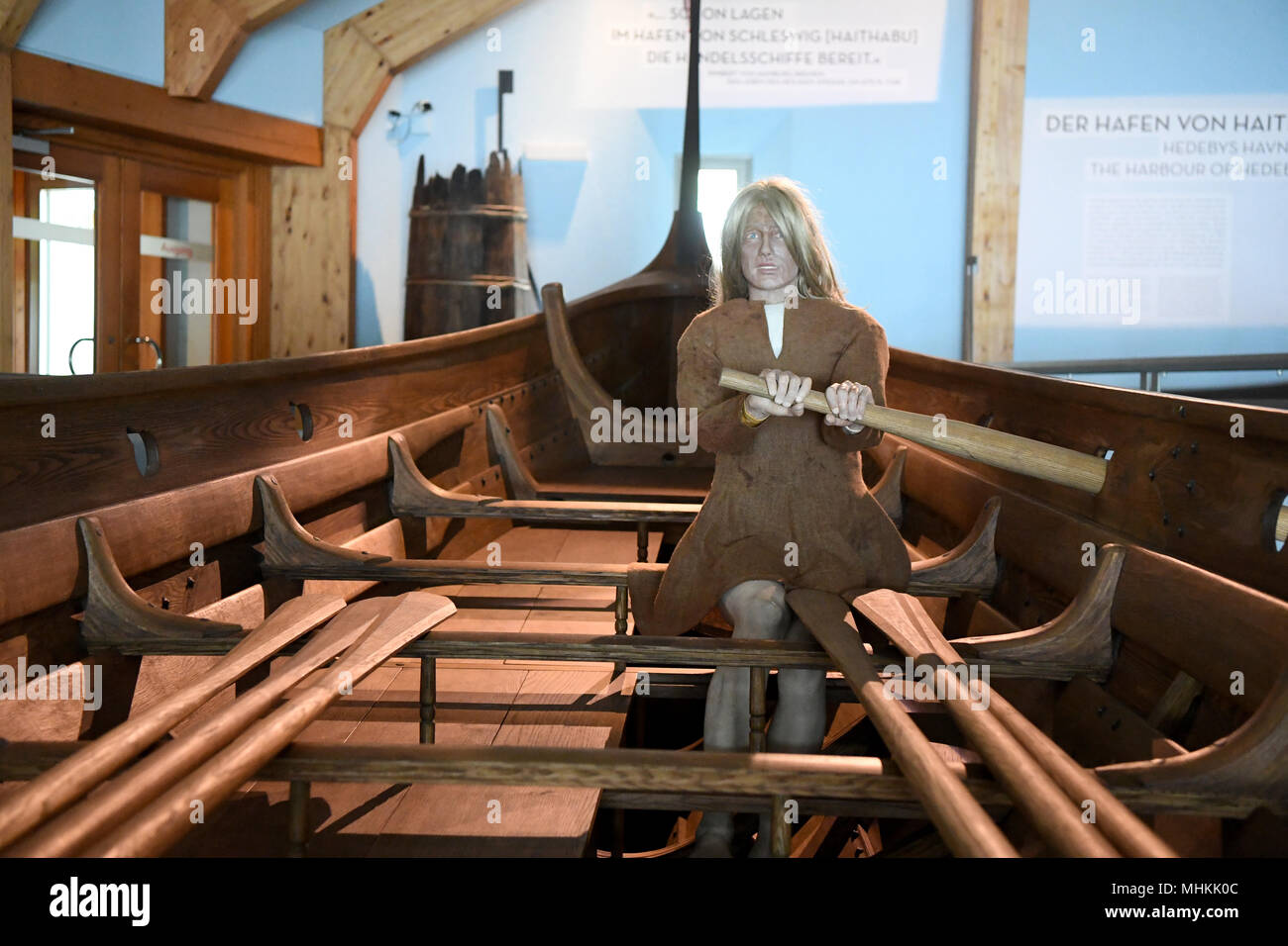 02 May 2018, Germany, Busdorf: A doll sitting in a boat at the Viking Museum Haithabu. The museum was closed for 18 months due to extensive renovation work and is to be reopened on 03 May 2018. Photo: Carsten Rehder/dpa - Stock Image