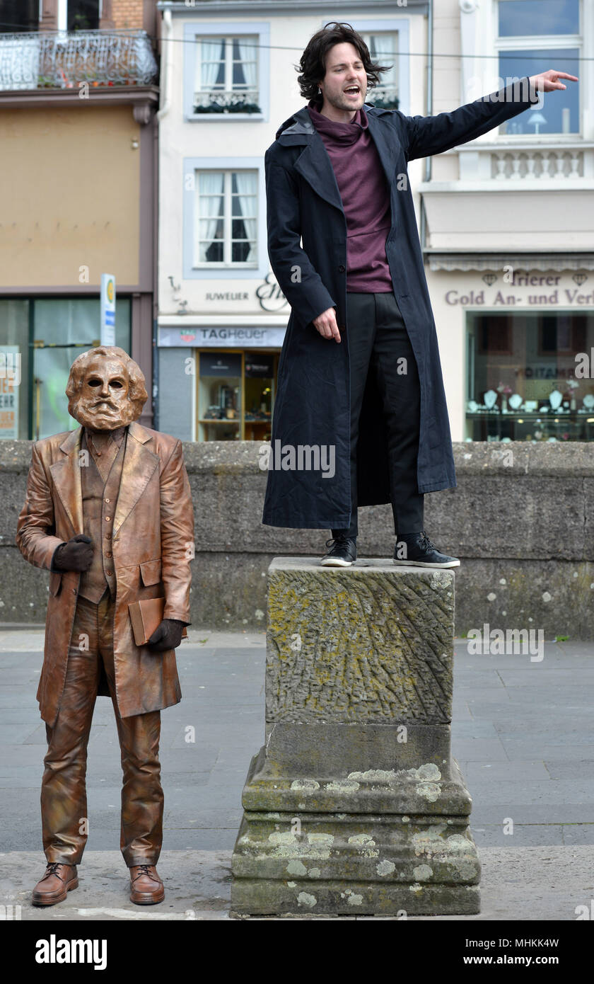 01 May 2018, Germany, Trier: Actor Tobias Schwieger (R) performing during the dress rehearsal of the piece «Marx! Love! Revolution!», a theatre piece by the Berlin author Johannes Kram, in front of the bronze statue of the old Karl Marx, represented by a masked extra. Photo: Harald Tittel/-/dpa Stock Photo