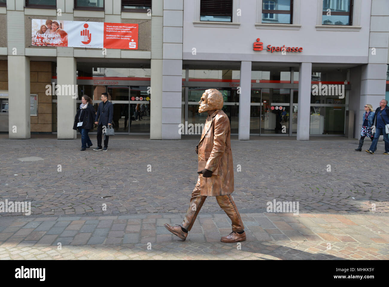 01 May 2018, Germany, Trier: An extra is dressed as the bronze statue of the old Karl Marx and walks from his plinth through the city as part of the dress rehearsal for the piece «Marx! Love! Revolution!», a theatre piece by the Berlin author Johannes Kram. Photo: Harald Tittel/-/dpa Stock Photo