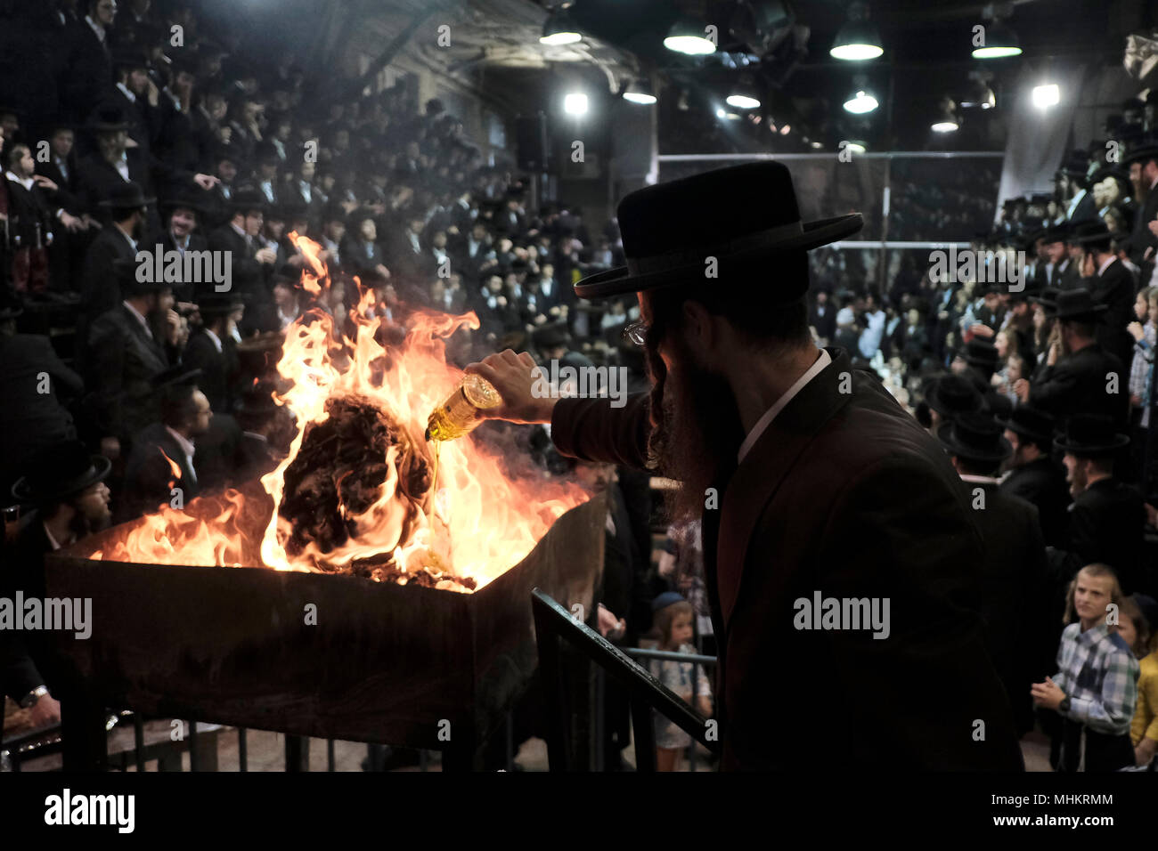 Jerusalem, Israel 02 May 2018. Ultra-Orthodox Jew pours oil into a bonfire in the Pinsk-Karlin Hassidic dynasty in Mea Shearim religious neighborhood during the celebration of Lag BaOmer holiday which marks the celebration, interpreted by some as anniversary of death of Rabbi Shimon bar Yochai, one of Judaism's great sages some 1800 years ago and the day on which he revealed the deepest secrets of kabbalah a landmark text of Jewish mysticism Credit: Eddie Gerald/Alamy Live News - Stock Image