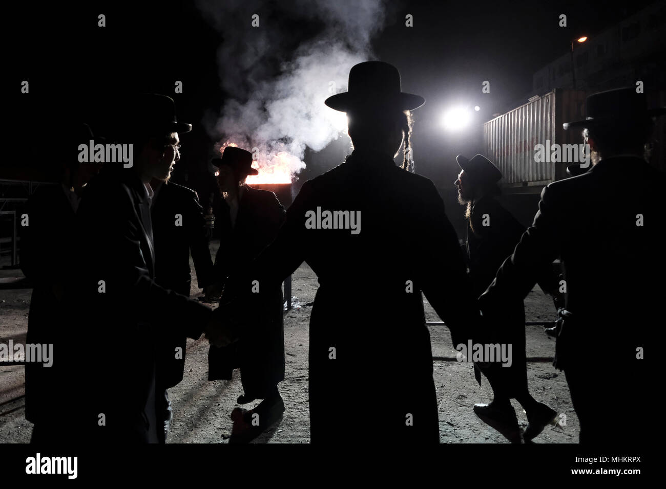 Jerusalem, Israel 02 May 2018. Ultra-Orthodox Jewish men from the Shomrei Emunim Hassidic dynasty dance as they light a giant oil fire in the Geula religious neighborhood during the celebration of Lag BaOmer holiday which marks the celebration, interpreted by some as anniversary of death of Rabbi Shimon bar Yochai, one of Judaism's great sages some 1800 years ago and the day on which he revealed the deepest secrets of kabbalah a landmark text of Jewish mysticism Credit: Eddie Gerald/Alamy Live News - Stock Image