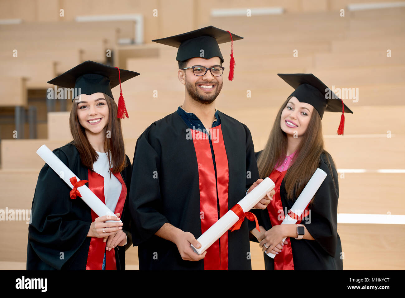 Smiling graduates keeping diplomas standing in spacy modern university classroom. Students wearing new black and red graduation gowns. Feeling happy, satisfied, laughing. Having brilliant future. - Stock Image