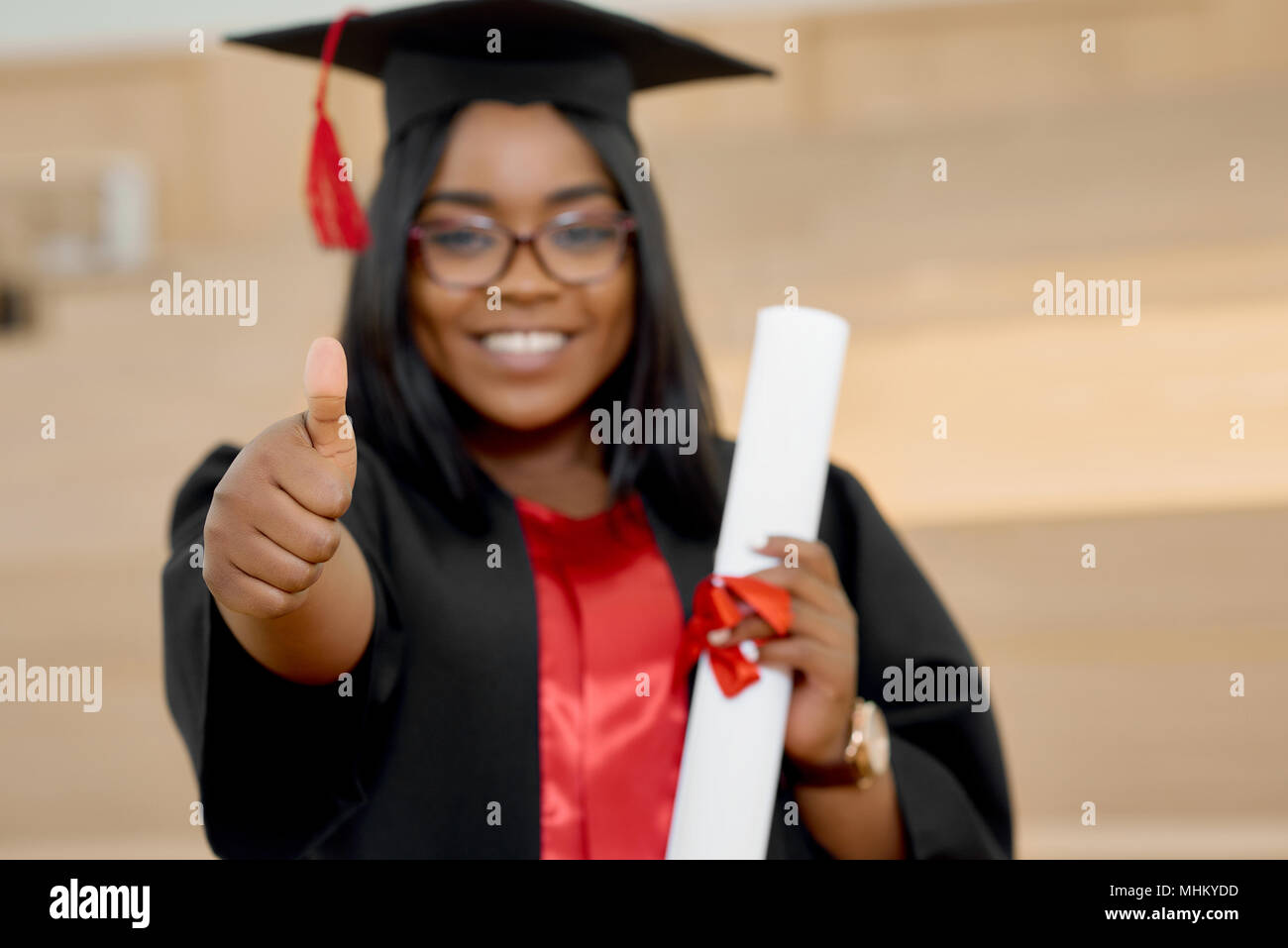Positive girl graduating from university. Student wearing black and red education gown and keeping diploma.Standing in classroom with wooden cascade desks. Smiling, feeling happy. Blurred focus. - Stock Image