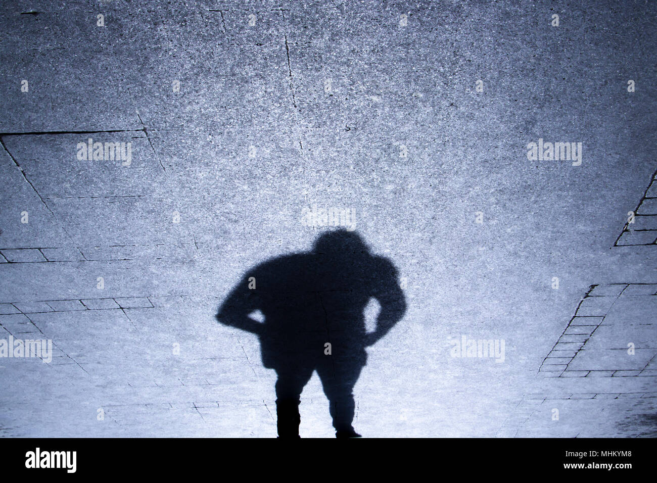 Upside down silhouette shadow of a man sending on patterened sidewalk from behind, in the night - Stock Image