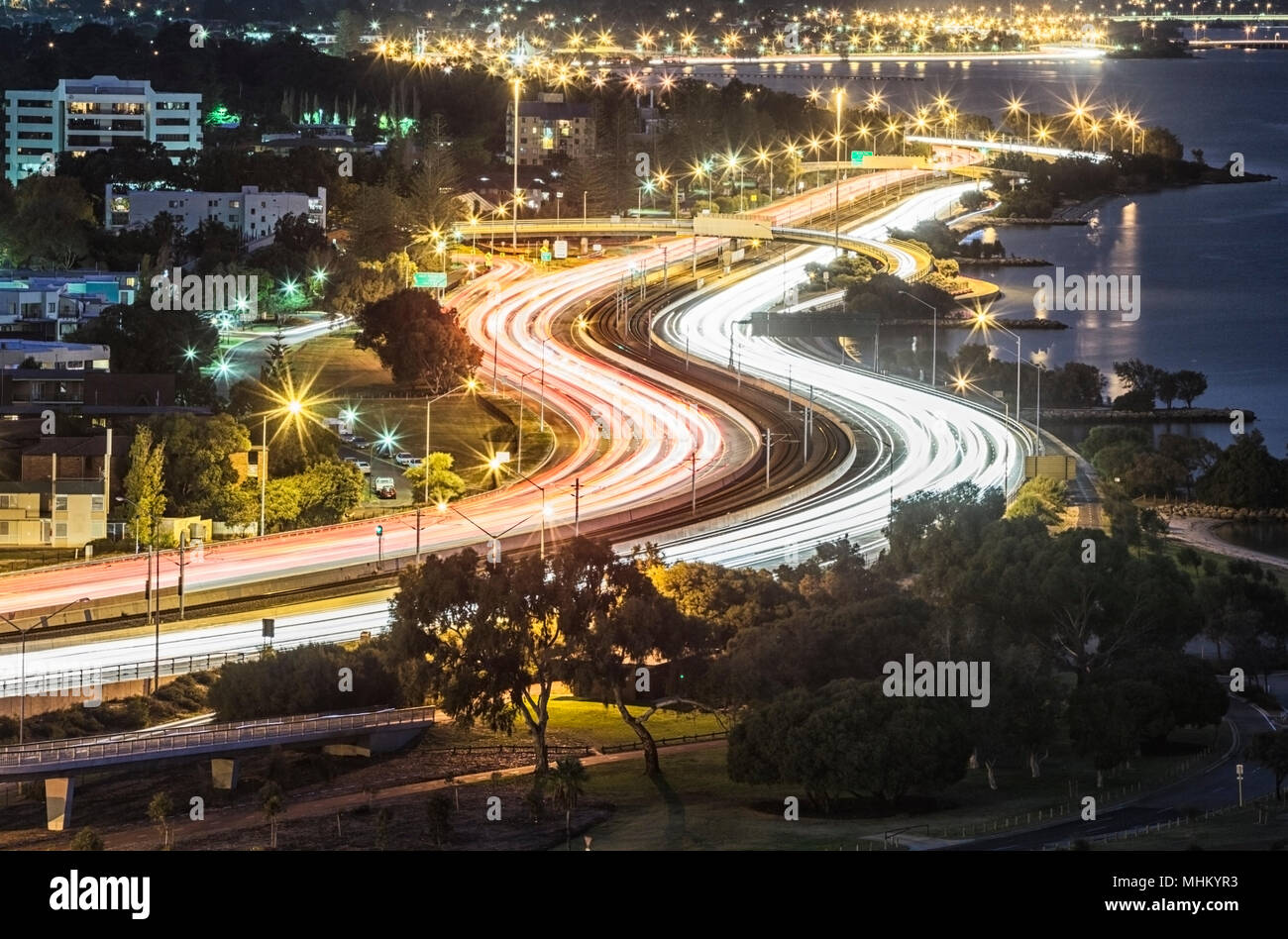 Light trails on a busy Mitchell Freeway at dusk. - Stock Image