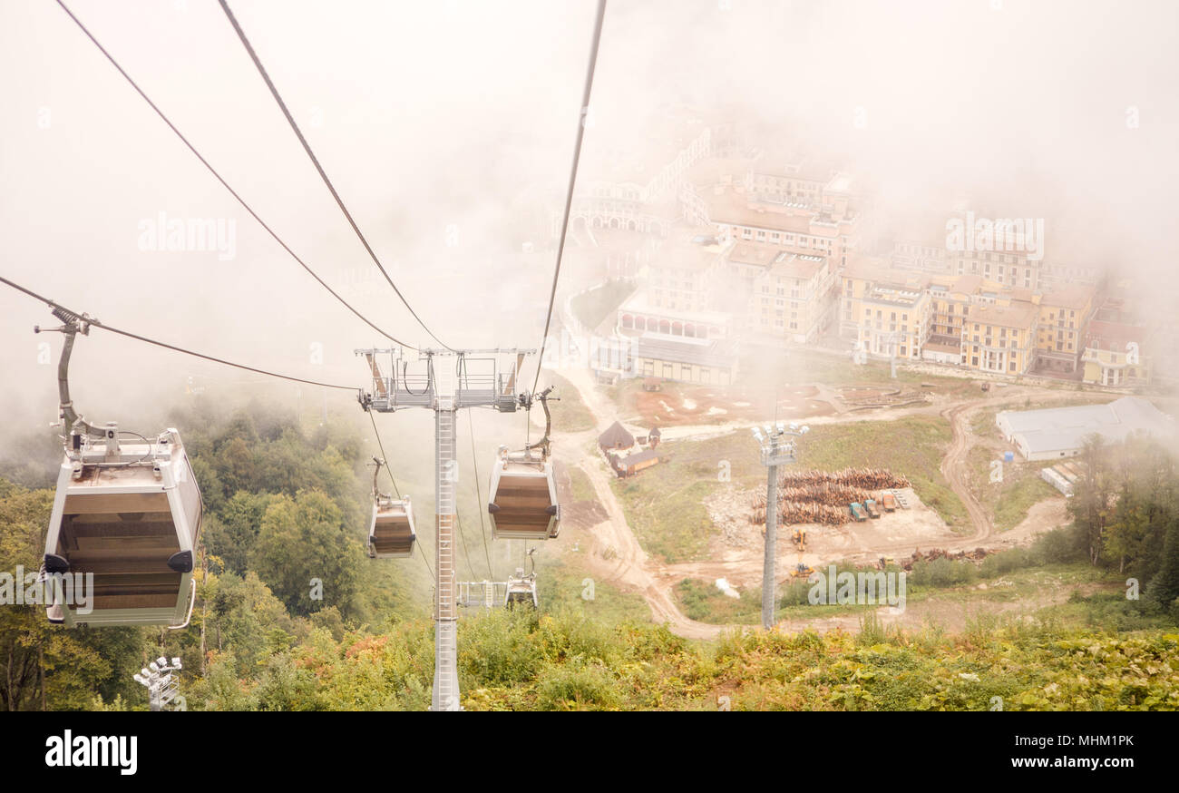 Picture of funicular in mountains against background of misty sky - Stock Image