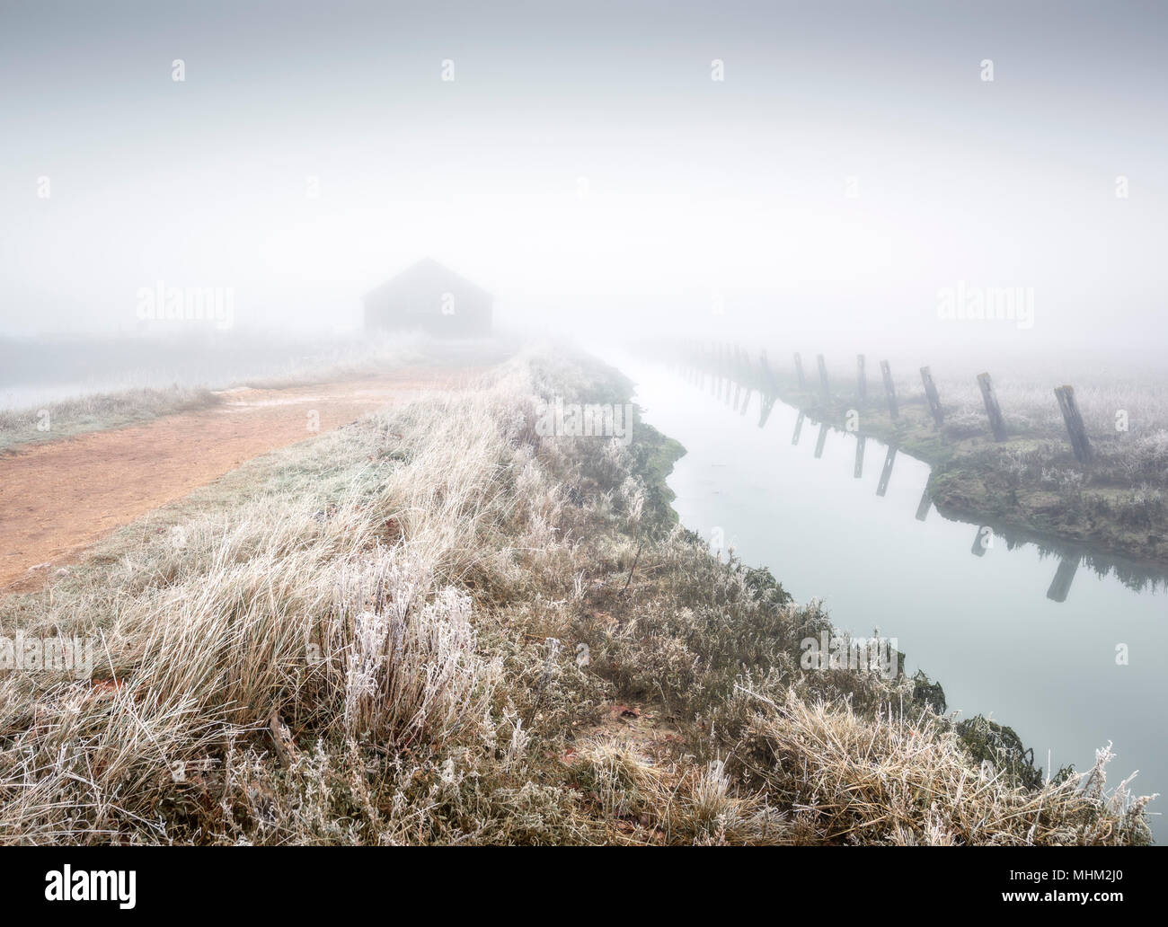 Boathouse in the eerie misty fog by the water in the frost - Stock Image