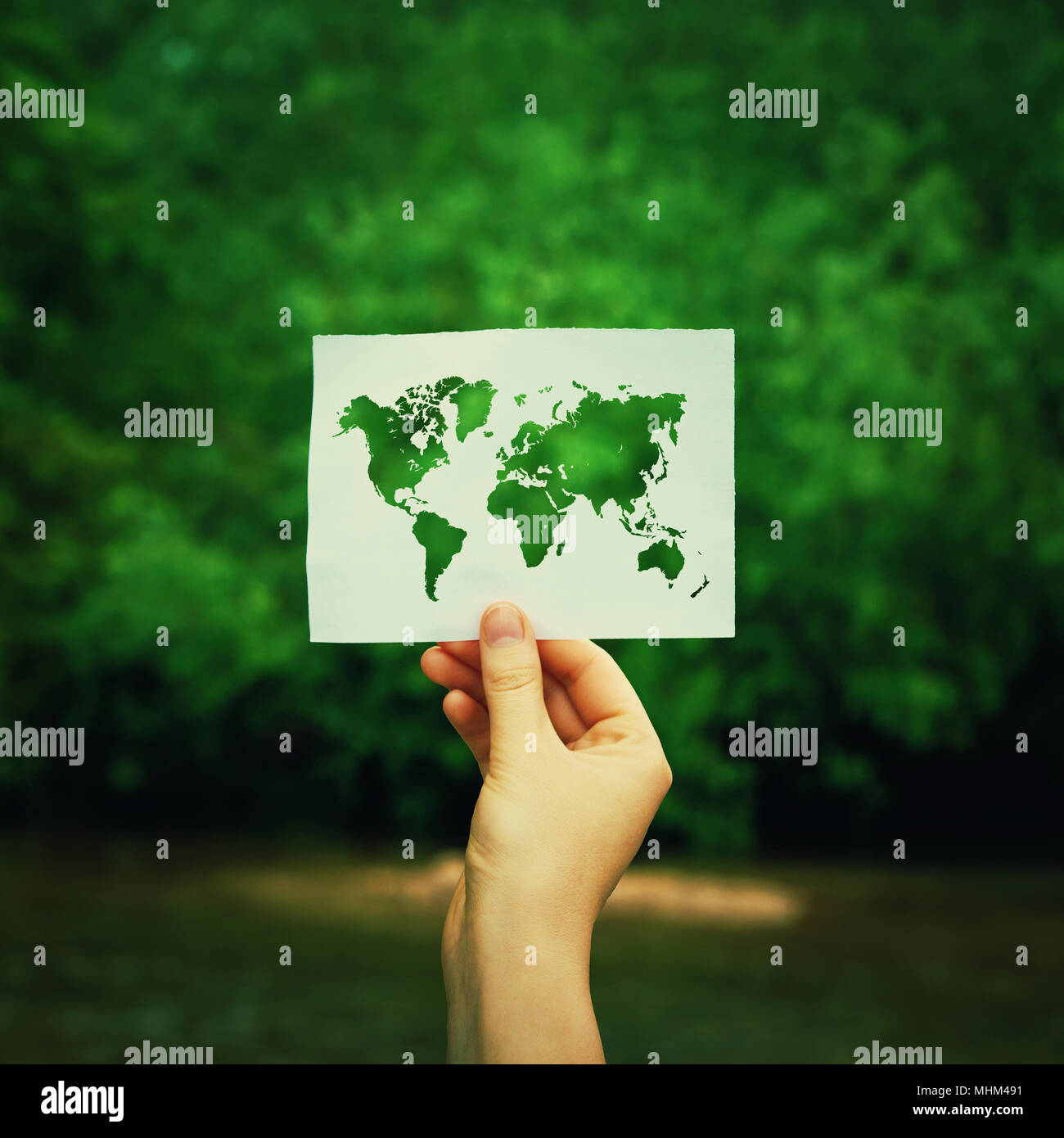 Woman hand holding a paper sheet with the world map over green forest nature background. Ecology and greening concept, global environmental issues wor - Stock Image