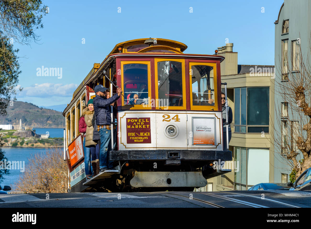 Street Cable Car - A cable car climbing up to the top of steep Russian Hill on Hyde St, with Alcatraz Island in background. San Francisco, CA, USA. - Stock Image
