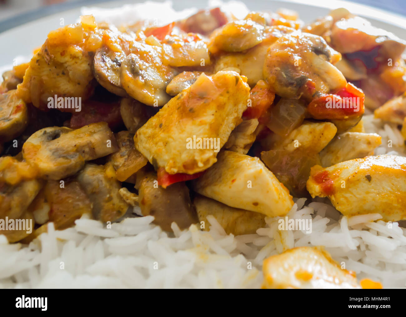 A close up of a chicken curry containing onions and peppers sitting on a bed of rice - Stock Image
