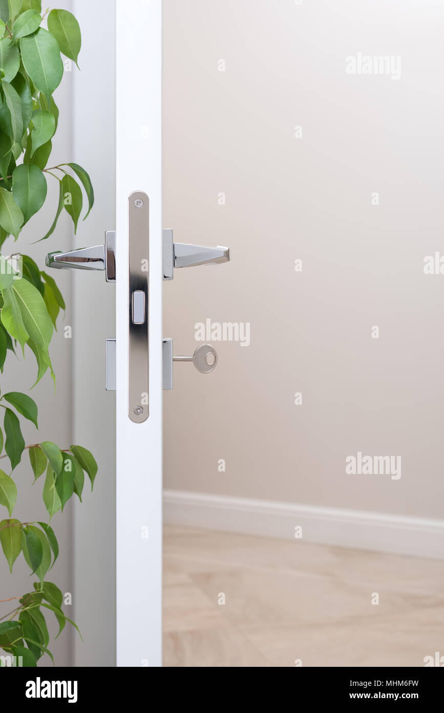 Closeup of the door lock with the key. Modern chrome handles. Light wall with free space in the background - Stock Image