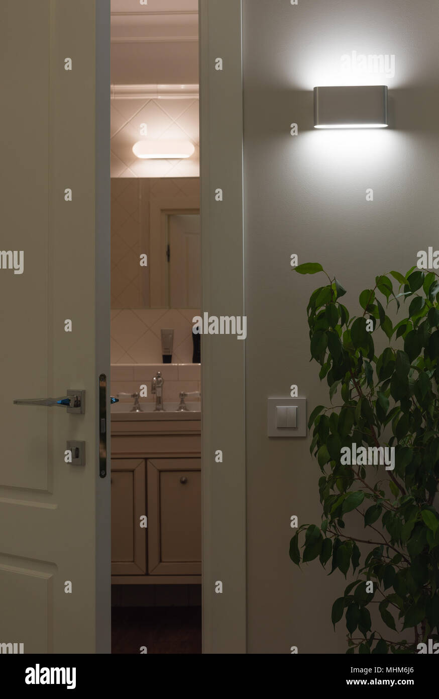 Wall LED lamps in the interior. Open white door to the bath. Comparison of led and halogen light - Stock Image