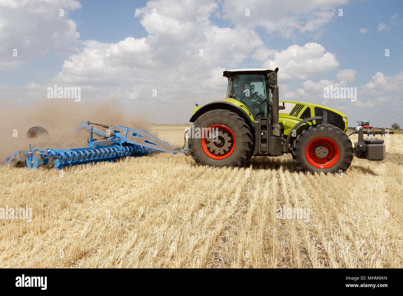 Tractor preparing land with plow, sunny summer day at agricultural field - Stock Image