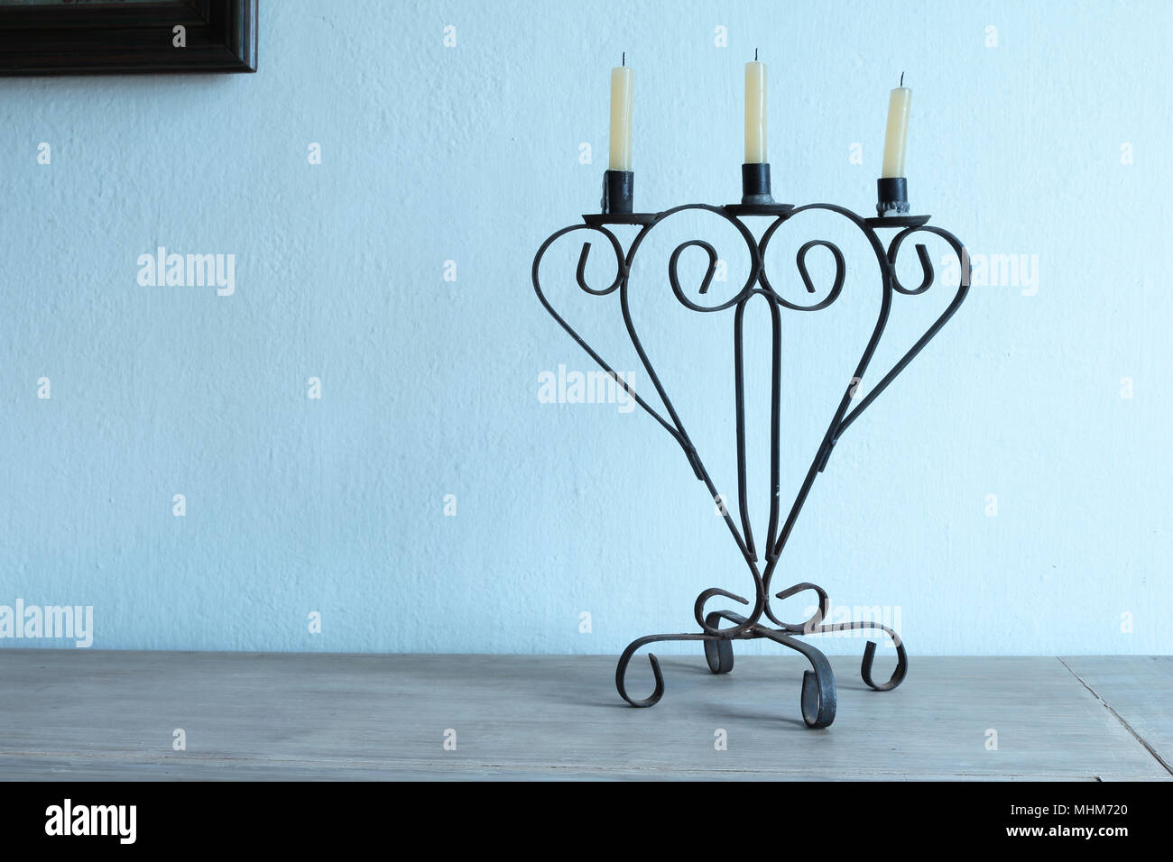 Old candle holder with three unlit candles - Stock Image