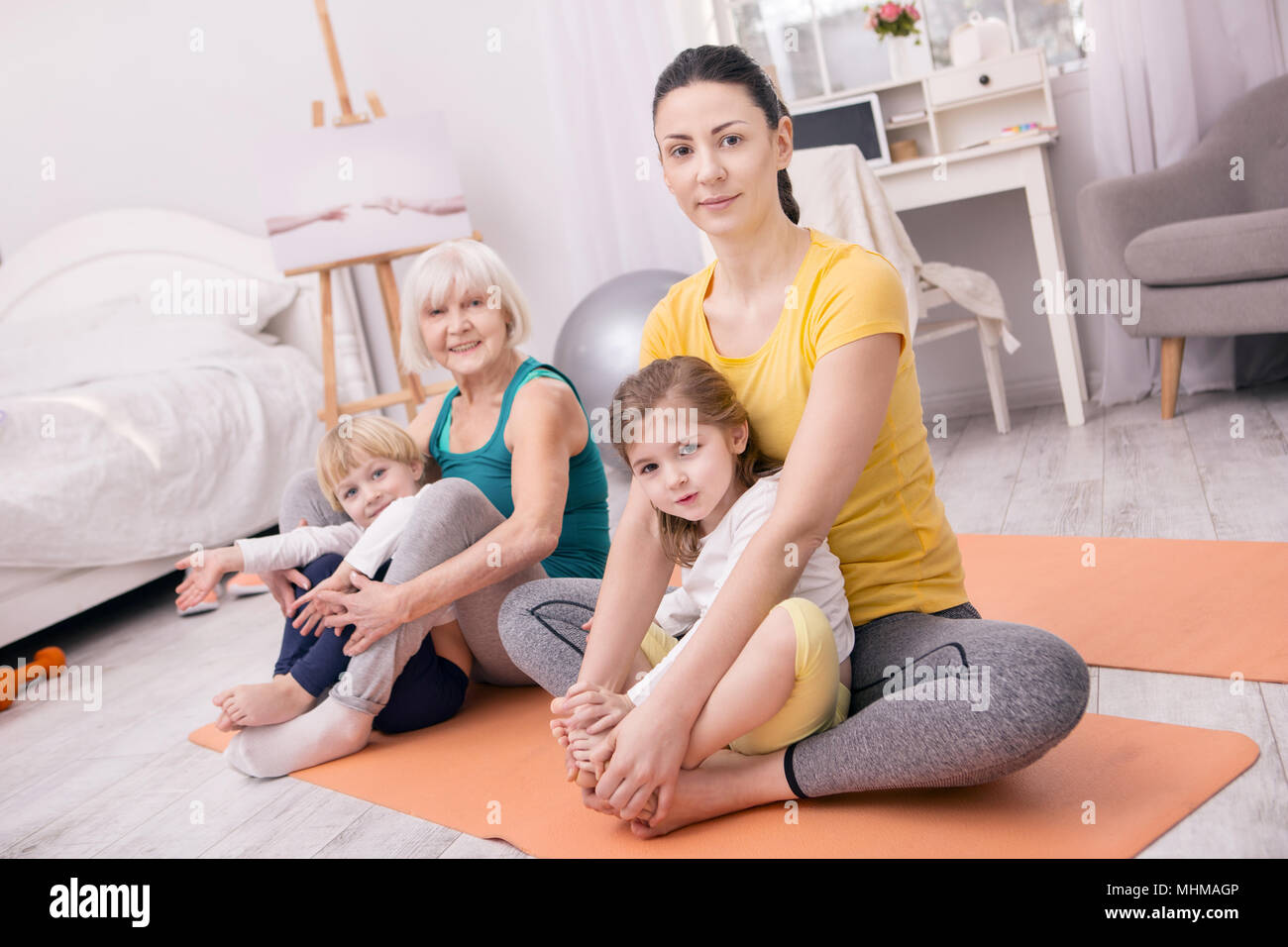 Cheerful women and kids doing yoga Stock Photo: 183000182