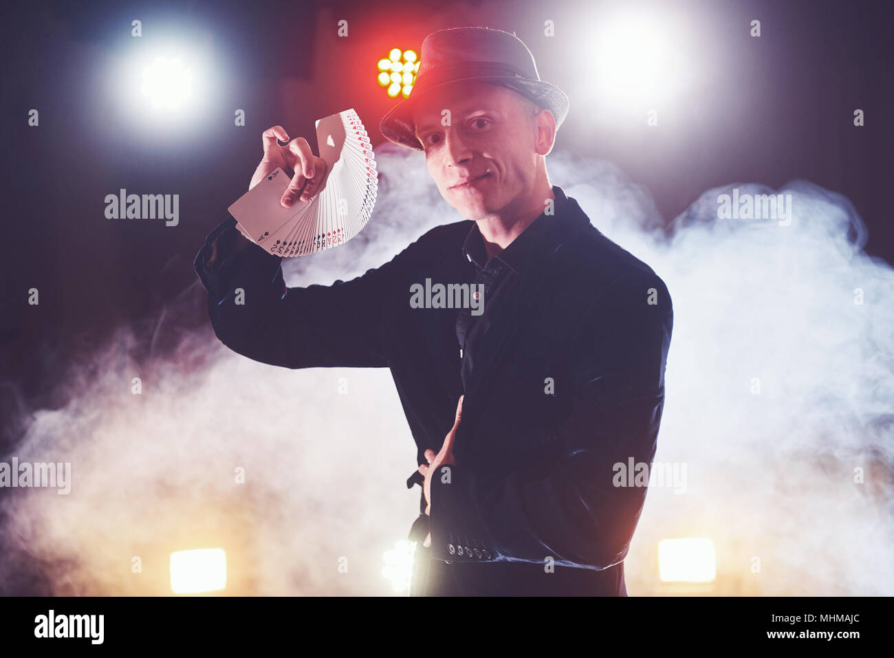 Magician showing trick with playing cards. Magic or dexterity, circus, gambling. Prestidigitator in dark room with fog Stock Photo