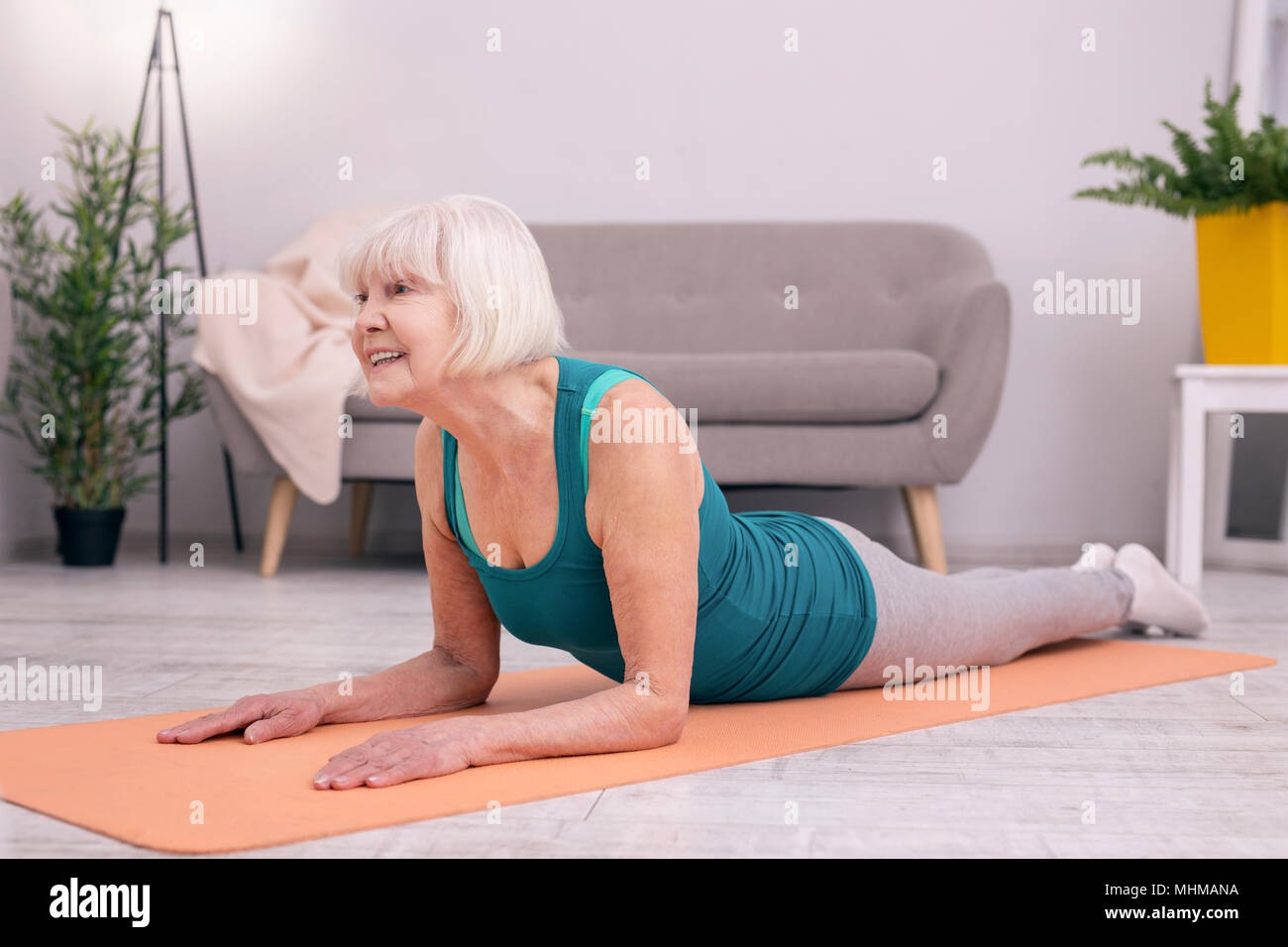 Pleasant senior woman exercising muscles of her neck - Stock Image