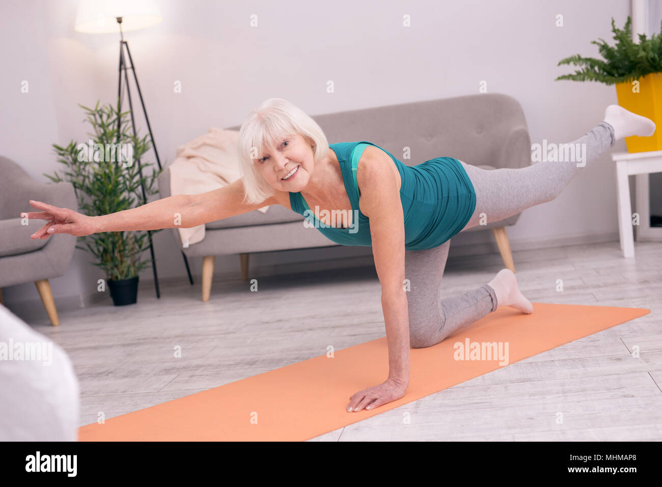 Pleasant senior woman standing on one knee and stretching - Stock Image
