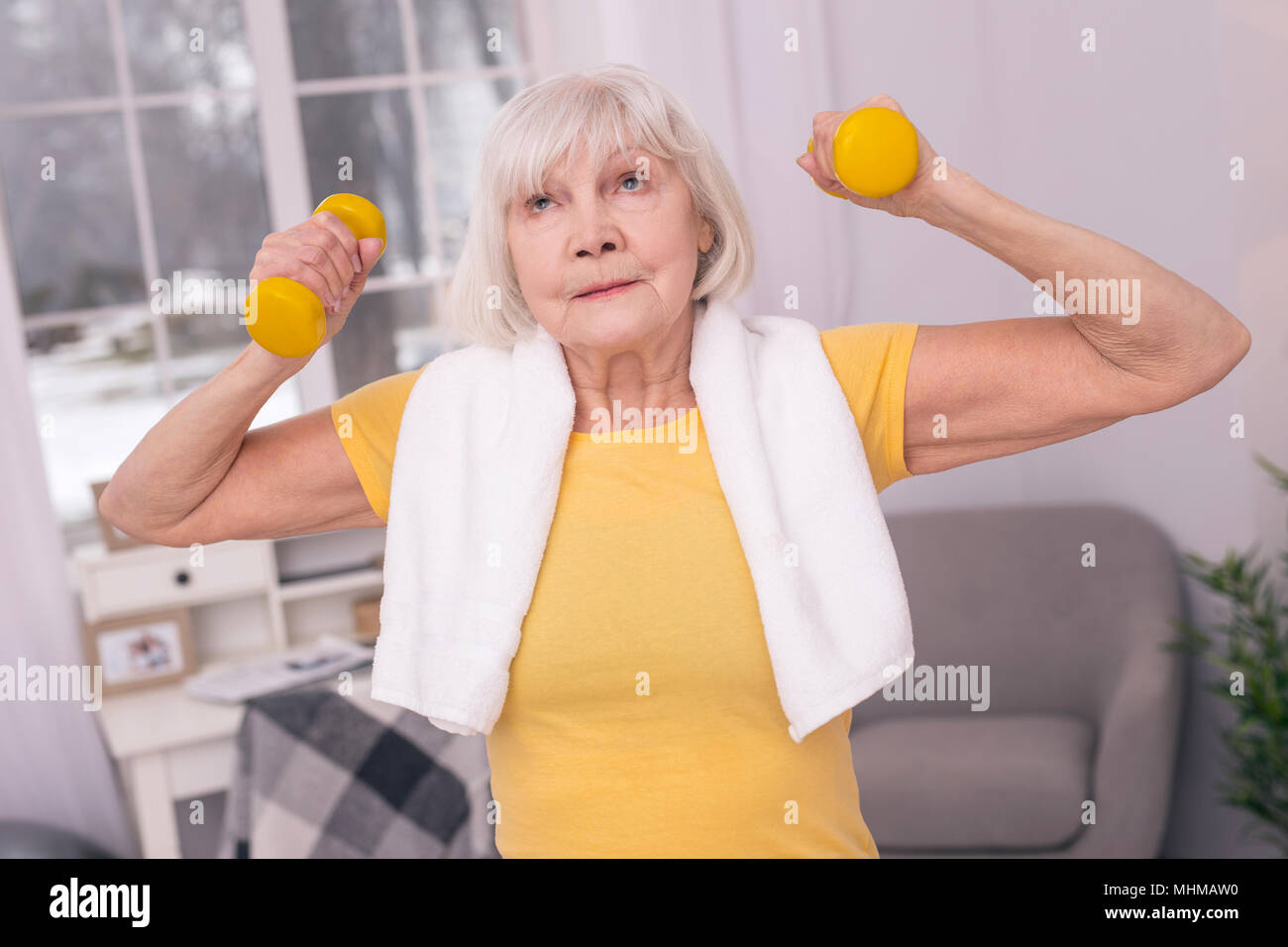Elderly woman being tired of exercising with dumbbells - Stock Image