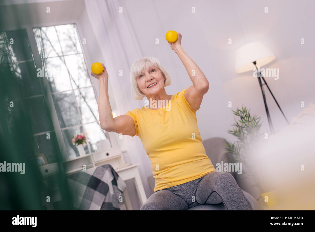 Charming senior woman smiling and lifting up dumbbells - Stock Image