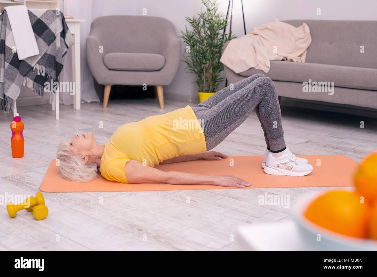 Pleasant elderly woman performing pelvic lift exercise - Stock Image