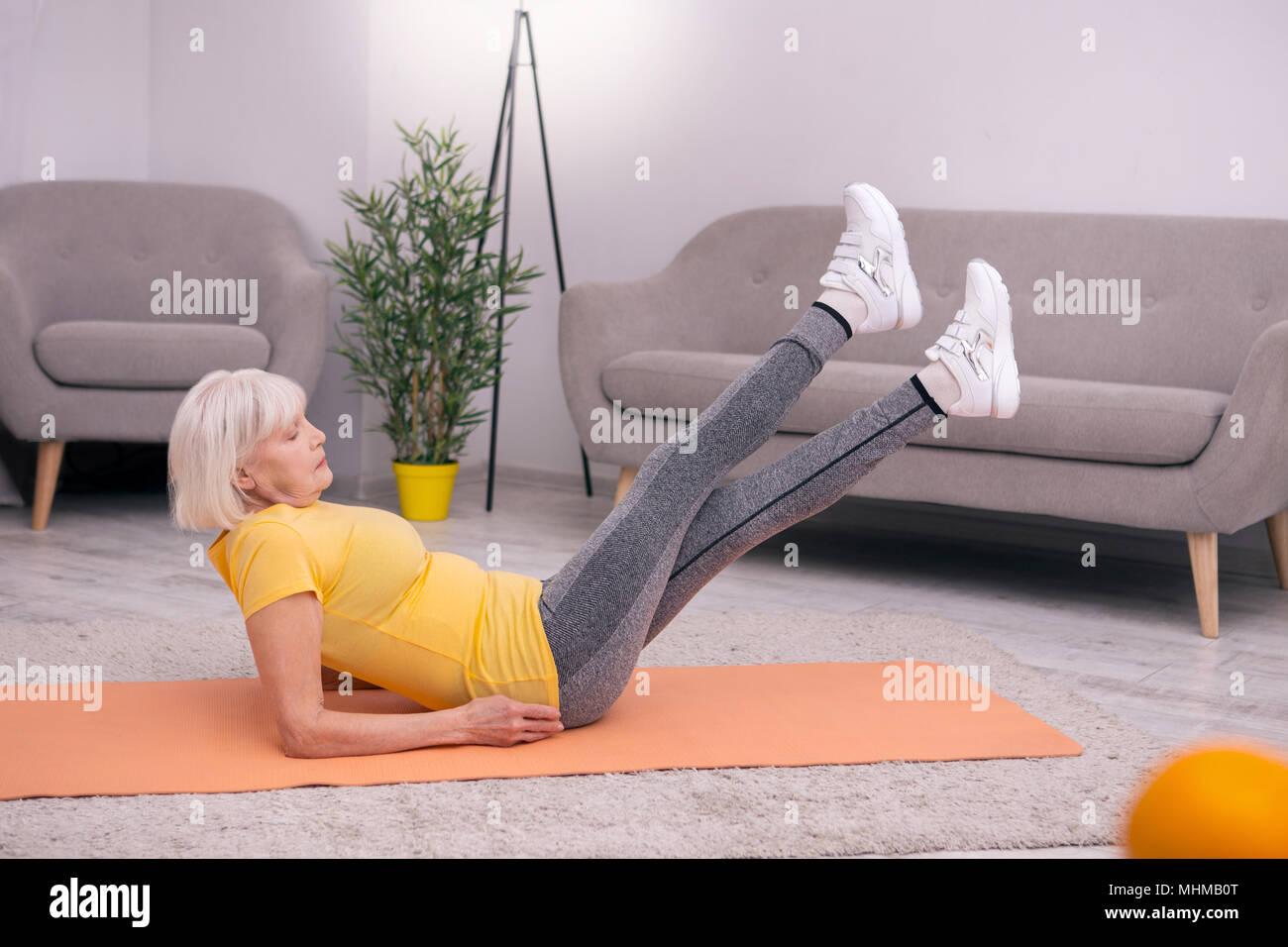 Pleasant senior woman doing leg lift exercise - Stock Image