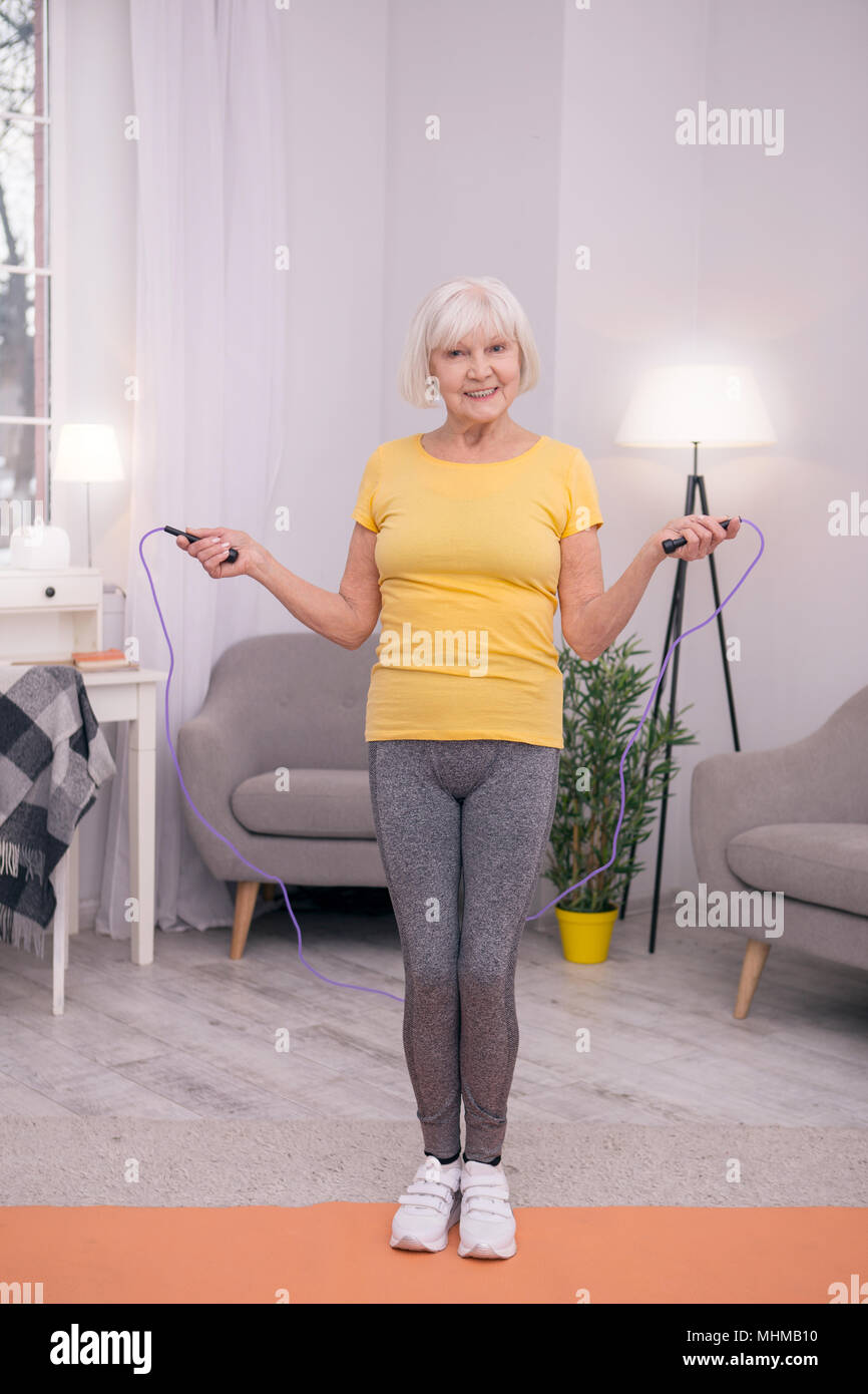 Upbeat elderly lady jumping rope at home - Stock Image