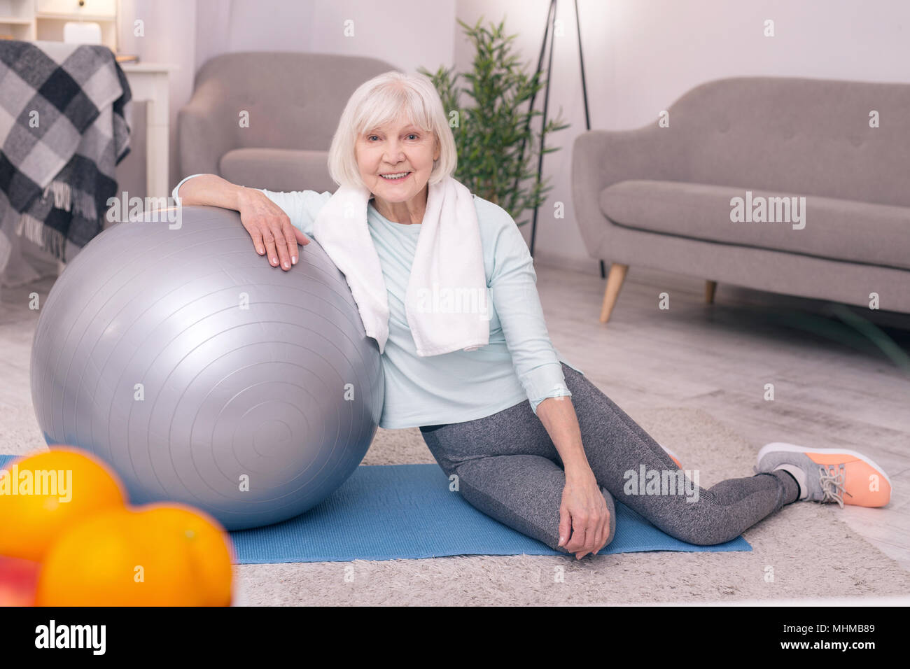 Charming elderly woman posing near exercise ball - Stock Image