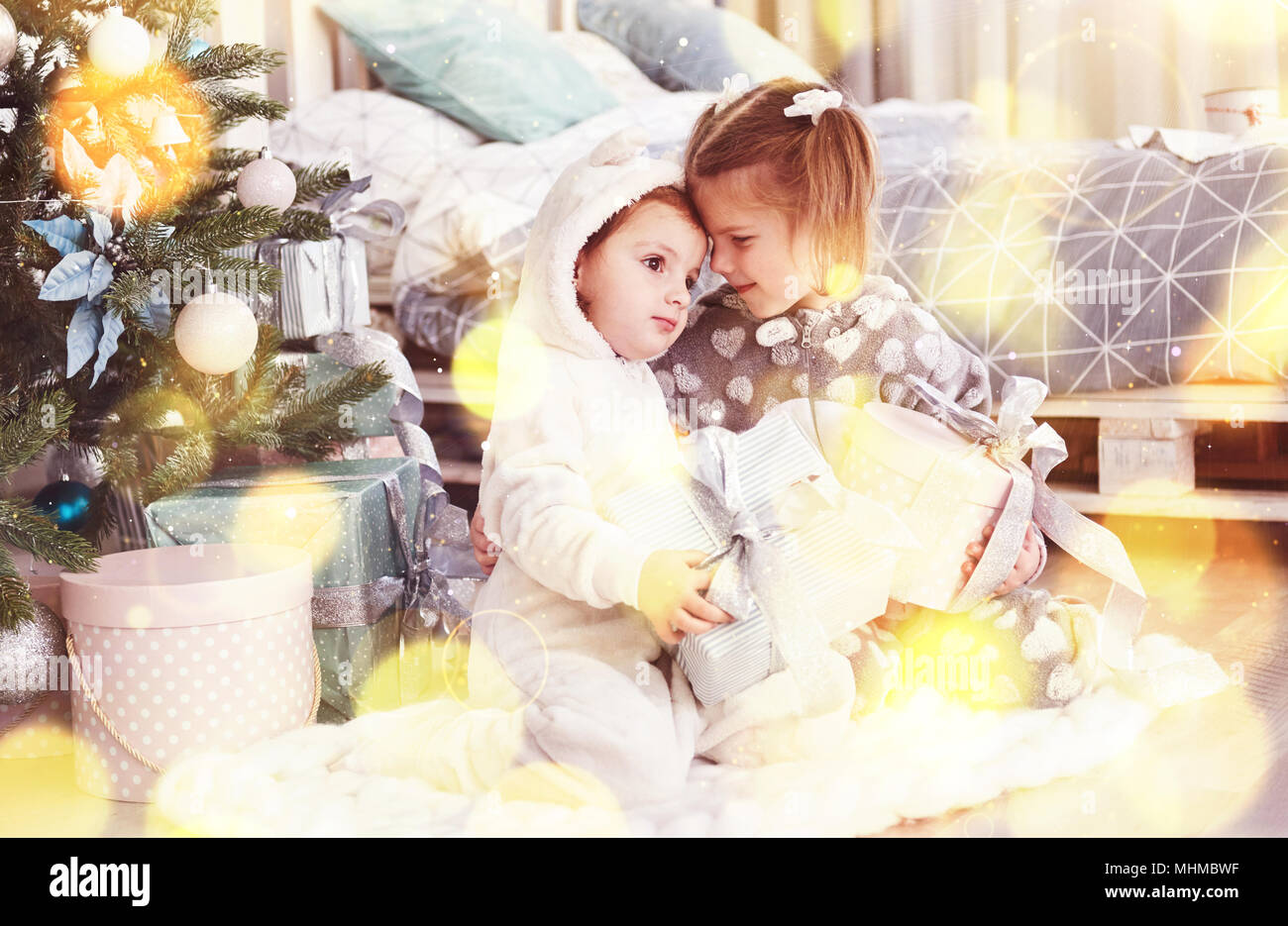 Two little sister girls open their gifts at the Christmas tree in the morning on the deck. - Stock Image