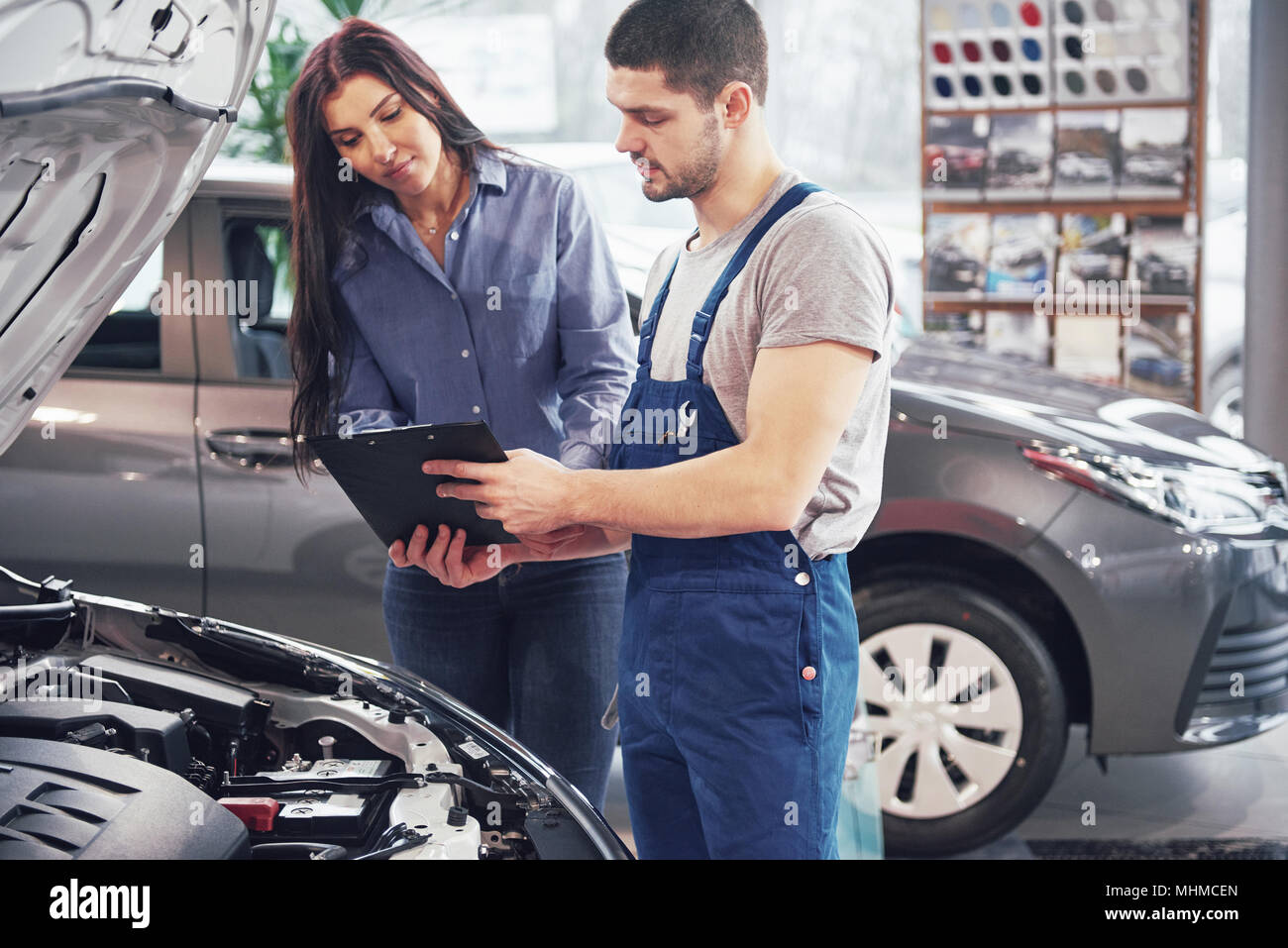 A man mechanic and woman customer discussing repairs done to her vehicle - Stock Image