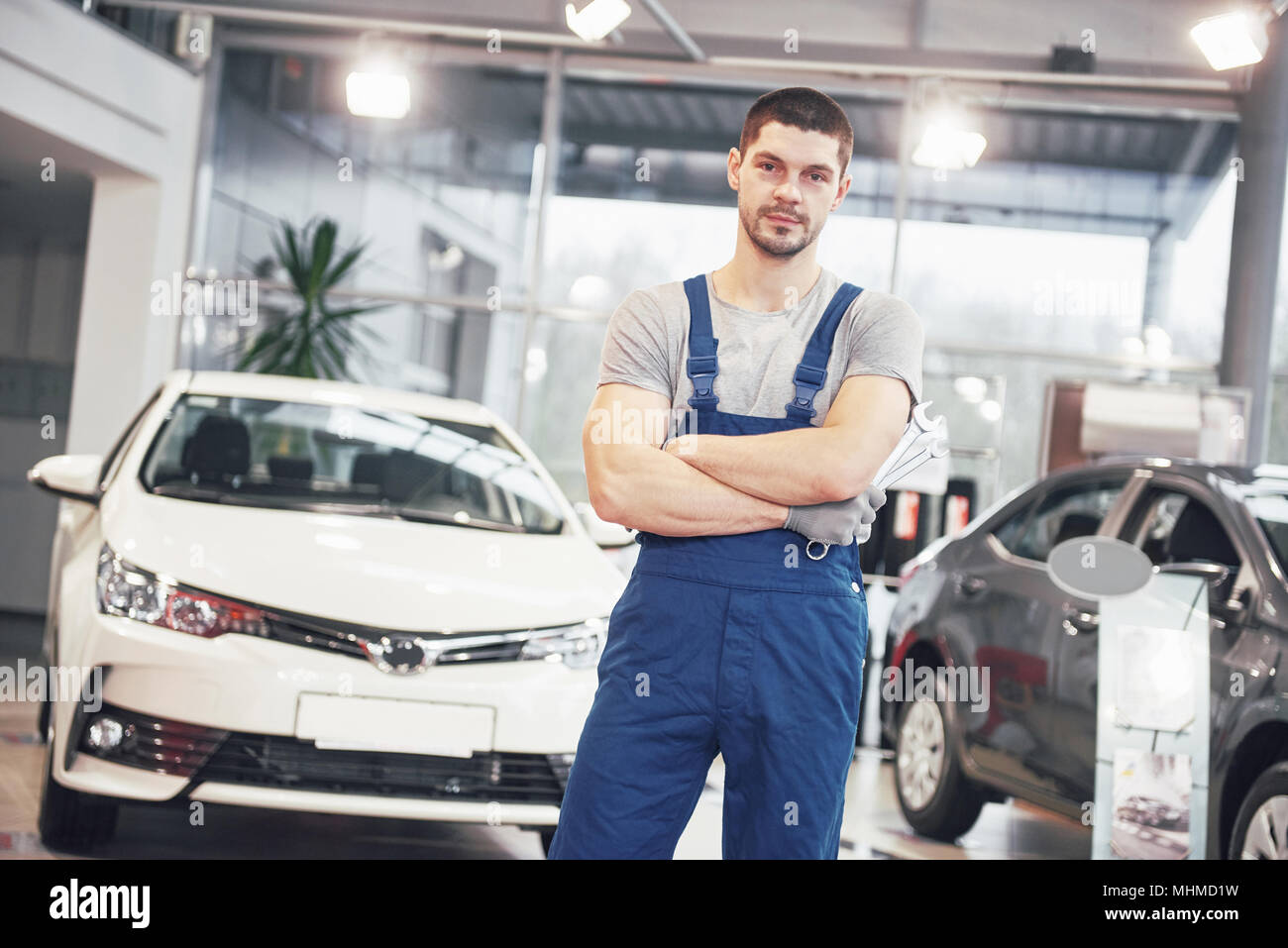 Hand of car mechanic with wrench. Auto repair garage - Stock Image