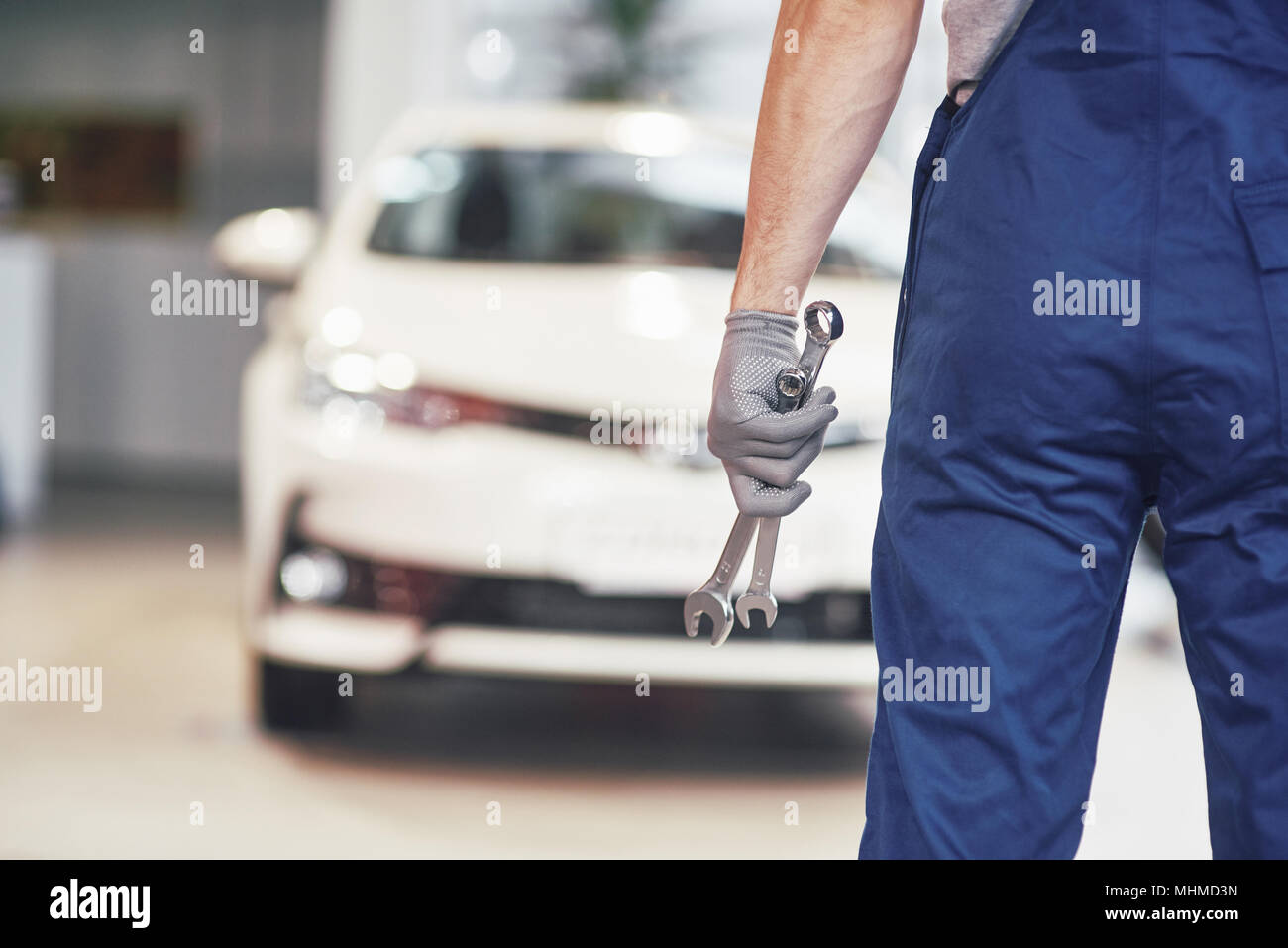 Hands of car mechanic with wrench in garage - Stock Image