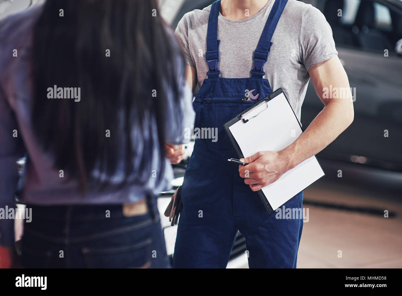 husband car mechanic and woman customer make an agreement on the repair of the car - Stock Image